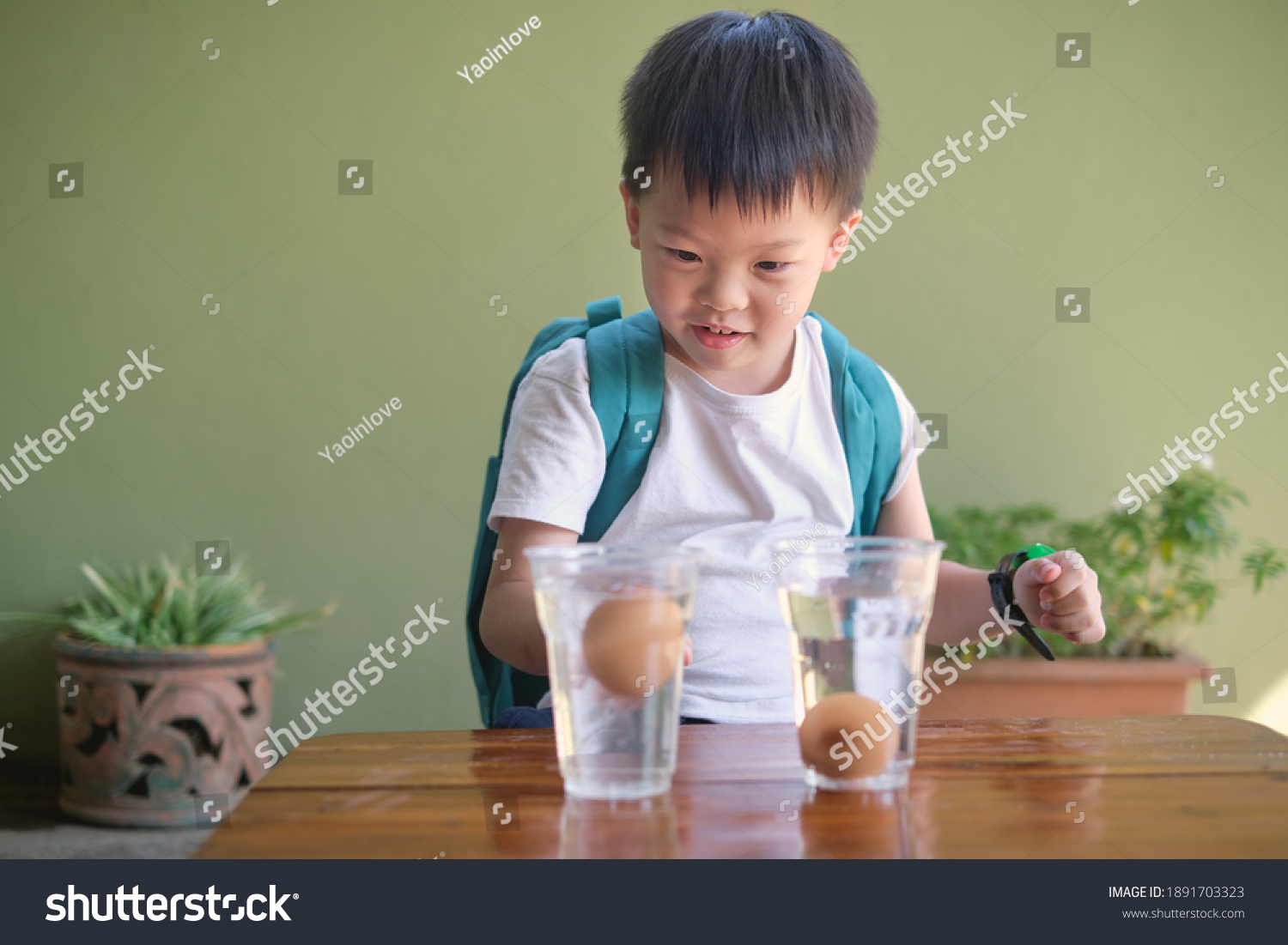 Happy smiling excited little Asian school kid studying science, doing fun and easy Floating Egg Science Experiment to learn about the density of salt water effect to floating and sinking of the eggs #1891703323