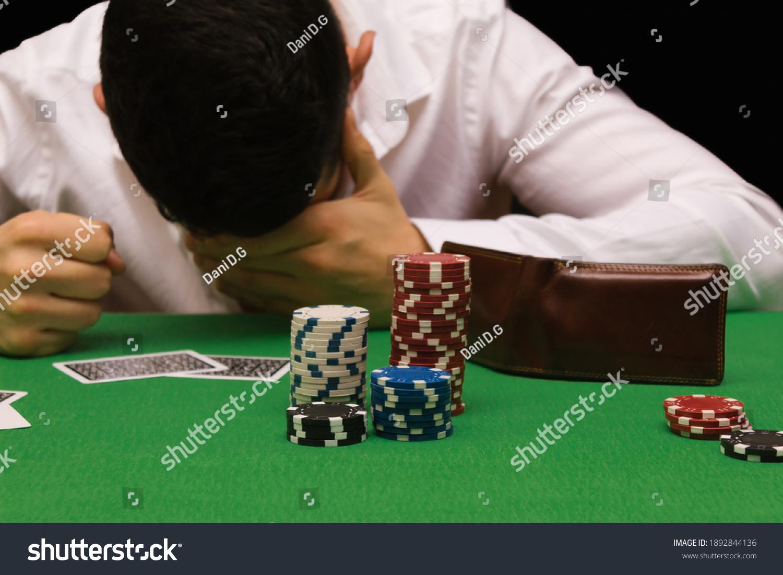 Devastated gambler man losing a lot of money playing poker in casino, gambling addiction. Divorce, loss, ruin, debt, ludopata concept #1892844136