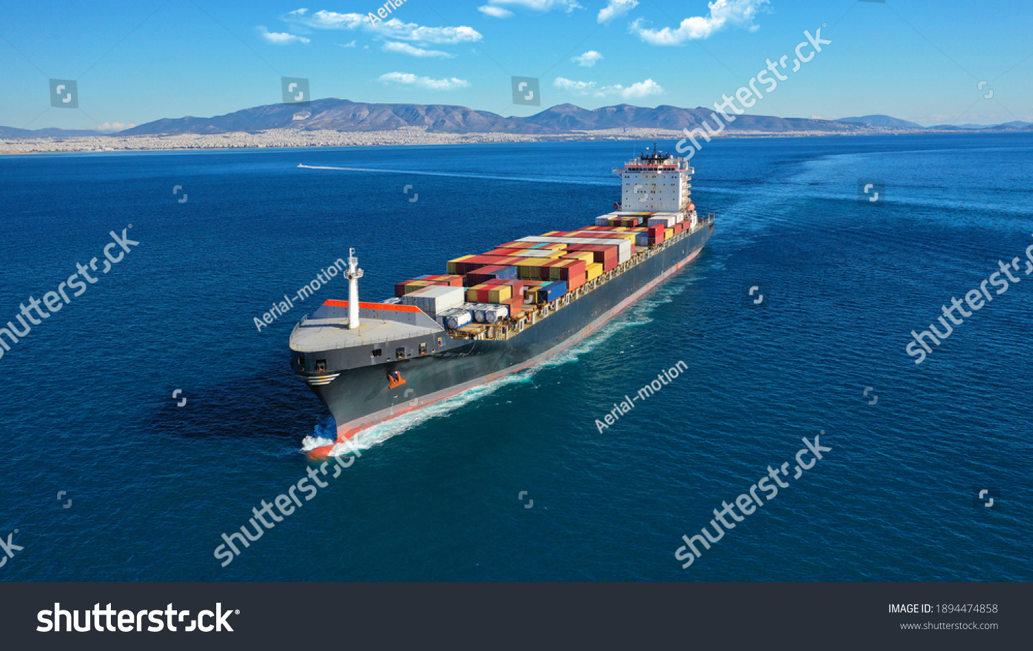 Aerial drone photo of industrial colourful vessel carrying heavy truck size containers cruising the Aegean deep blue sea #1894474858