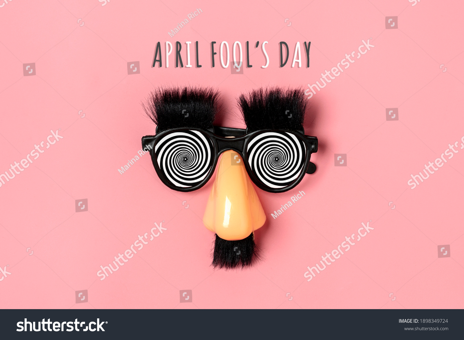 funny face - fake eyeglasses, nose and mustache on pink background Happy fools day  concept  1st April party Holiday card #1898349724