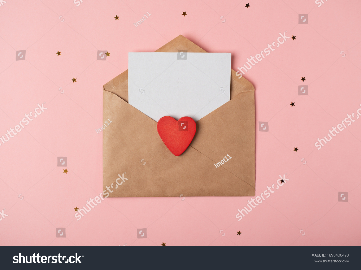 Craft envelope with a blank sheet of paper inside and red wooden heart on the rose background. Romantic love letter for the Valentine's day concept. Space for text. #1898400490