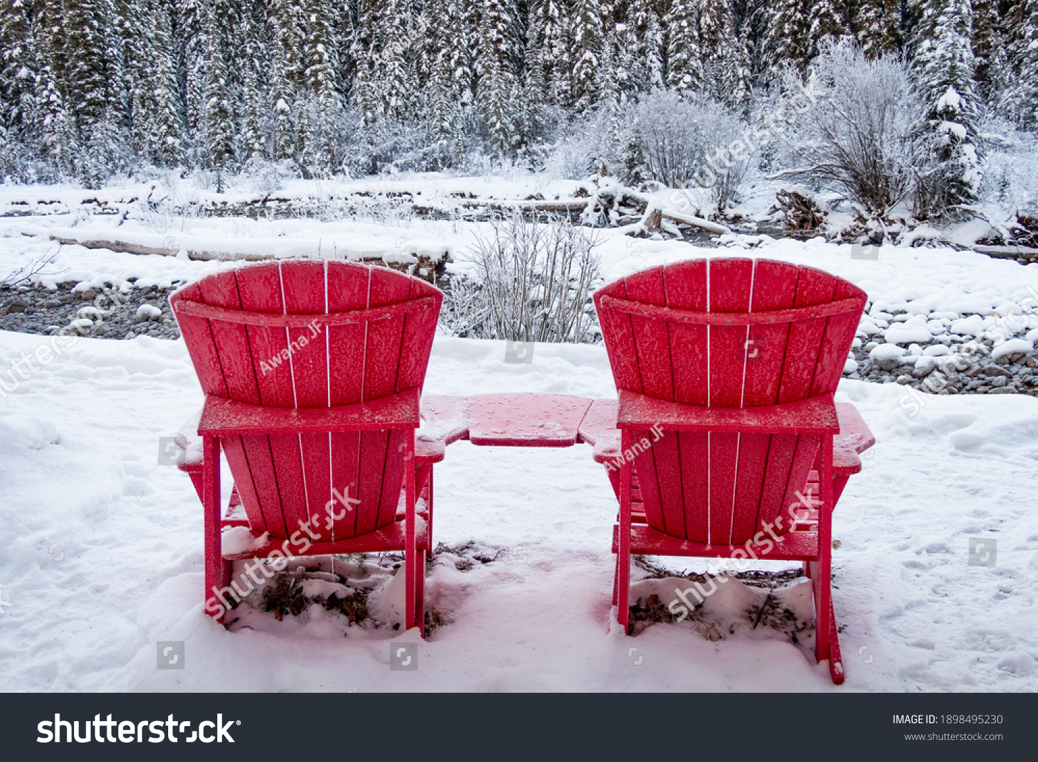 Two red Adirondack chairs nearby Maligne river in winter