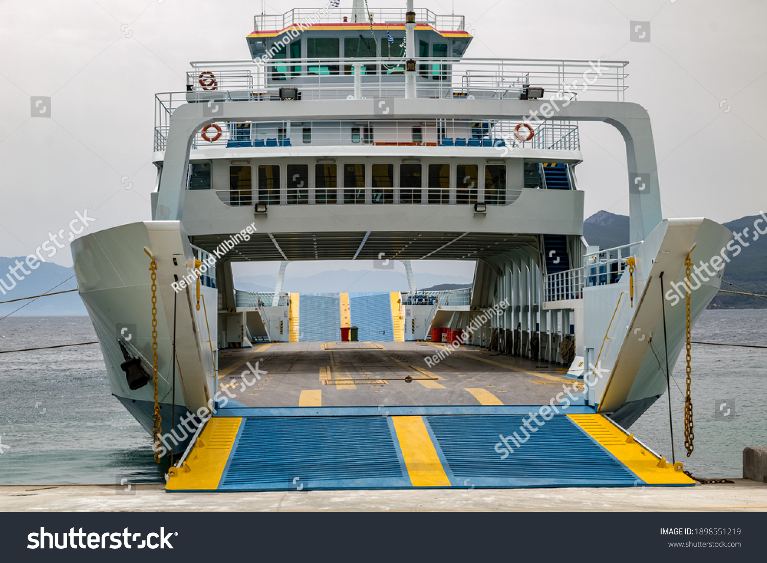 a ferry has docked in the port and is waiting for passengers and cars with an open loading ramp. #1898551219