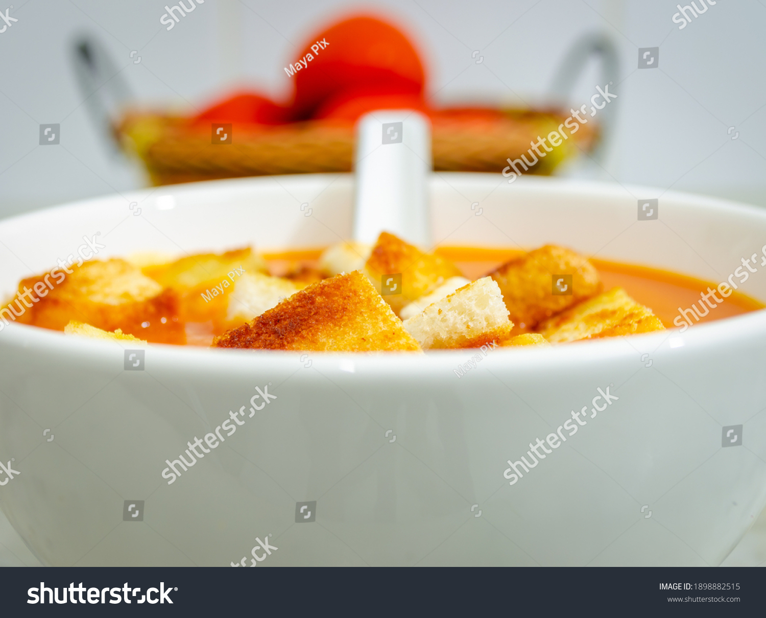 Beautiful View of Tomato Soup with bread croutons in a bowl with soup spoon and tomatoes in a basket in the background