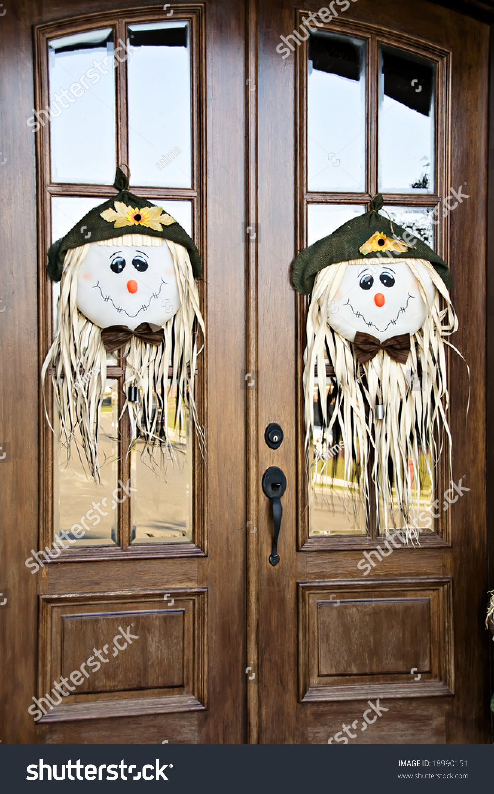 Two beautiful wooden doors dressed with scarecrow heads for Beautiful wooden doors picture collection