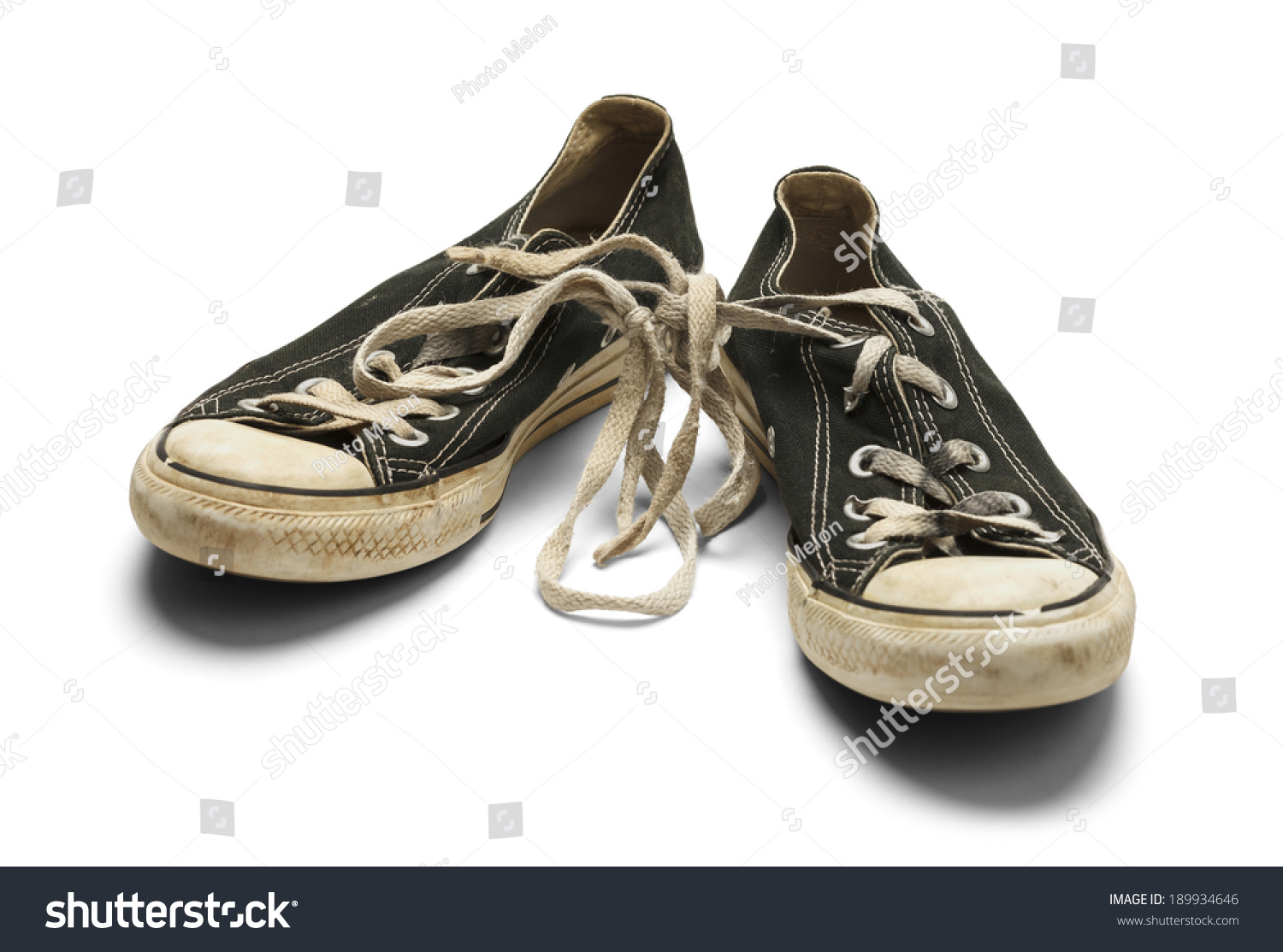 27f56747b9f7 Old Dirty Worn Pair of Canvas Shoes With Knot in Shoe Laces Isolated on White  Background