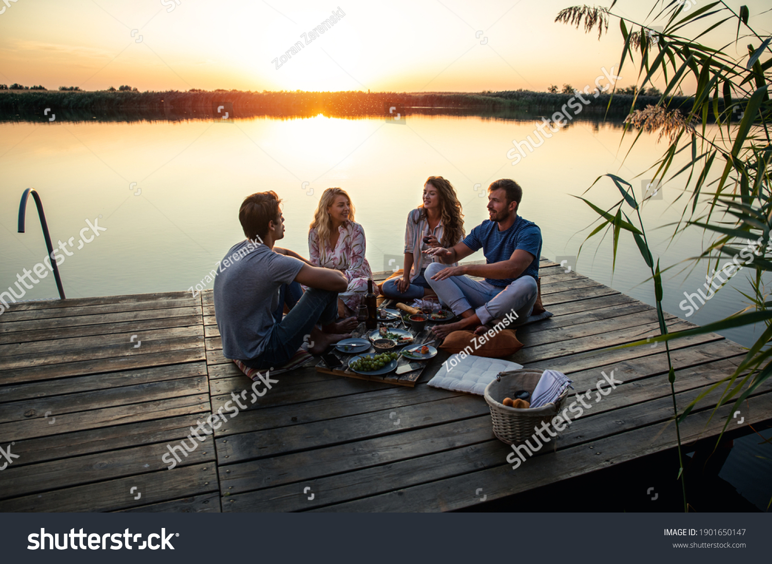 Group of friends having fun on picnic near a lake, sitting on pier eating and drinking wine. #1901650147