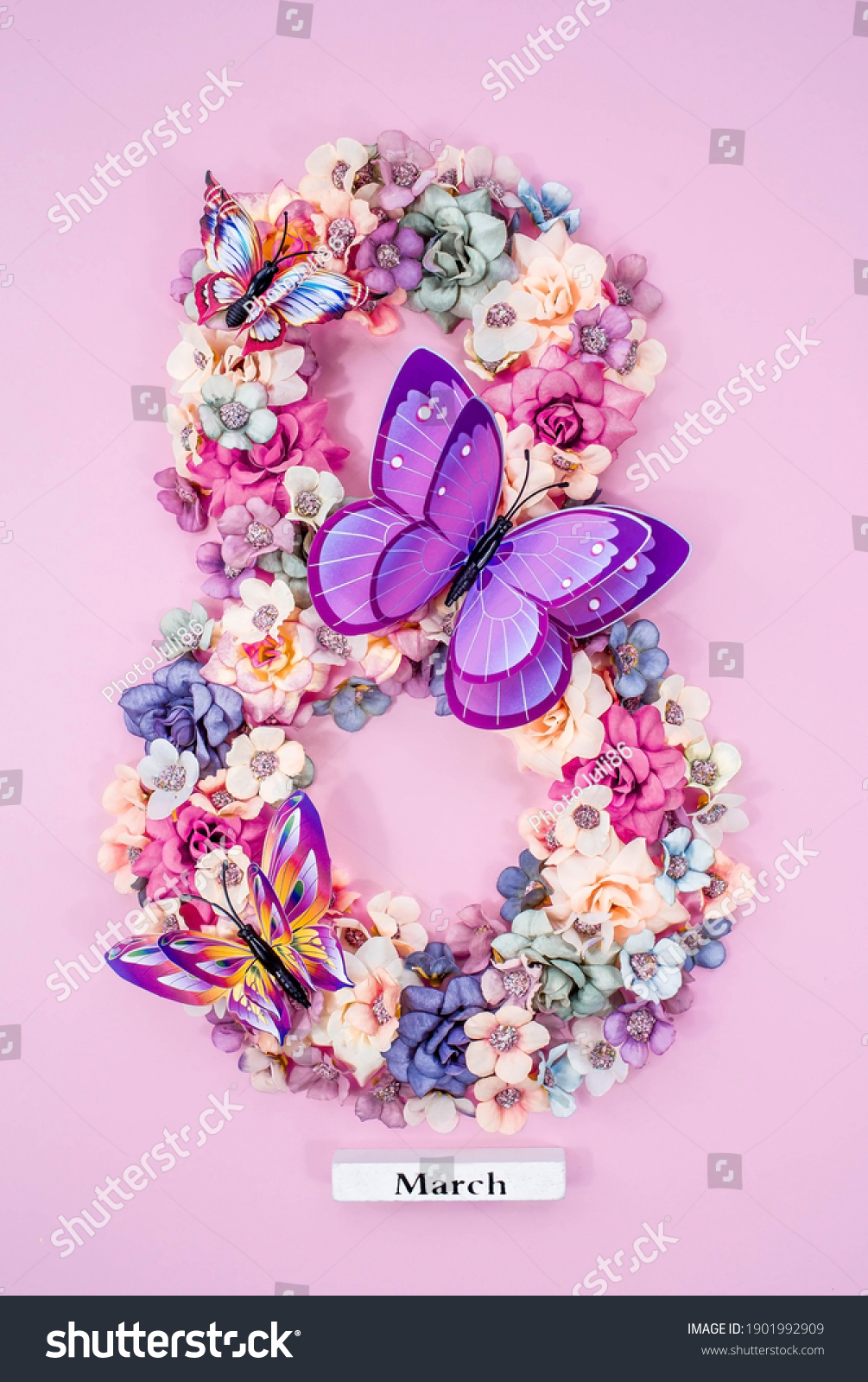International Women's Day. Banner, flyer, beautiful postcard for March 8. Flowers and butterflies in the shape of the number eight on a pink background. #1901992909