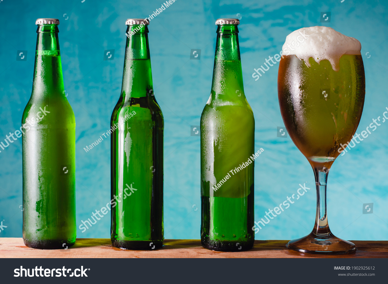 Three green bottles with beer, a glass of beer with foam, on blue background.
