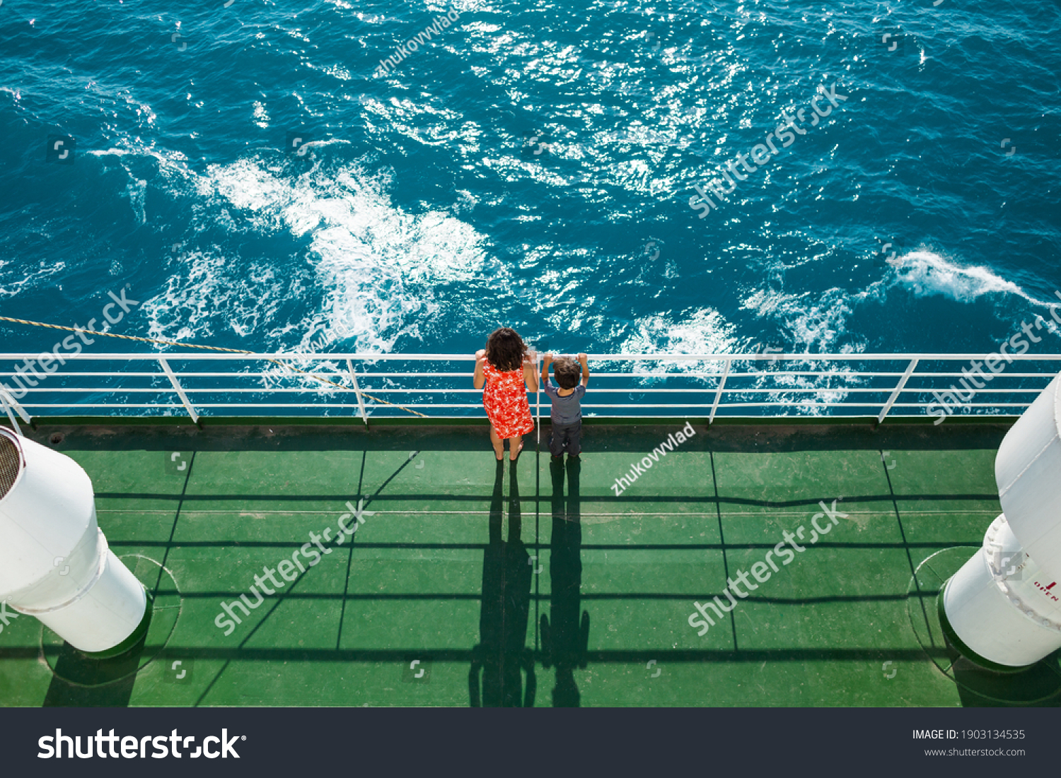 The family is sailing on a cruise ship, a mother with  son are standing at the fence on the ship and looking at the sea, traveling by ferry, a boy with mom are sailing on a ship. #1903134535