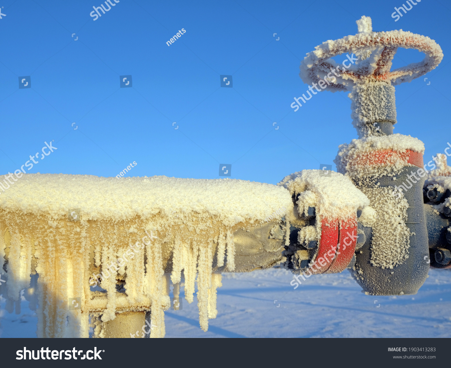 Gas valve and high pressure pipe. Oil and gas industry. Frozen icicles #1903413283