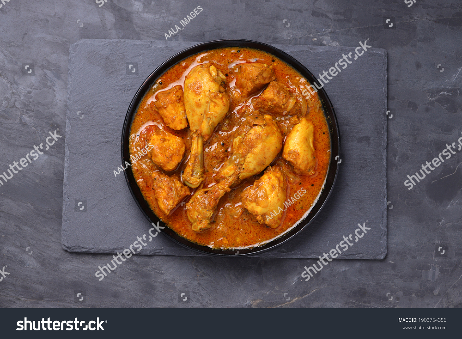 Chicken curry or masala,Kerala style chicken curry using fried coconut in traditional way and arranged in a black  ceramic vessel which is placed on a graphite sheet with grey background,isolated. #1903754356