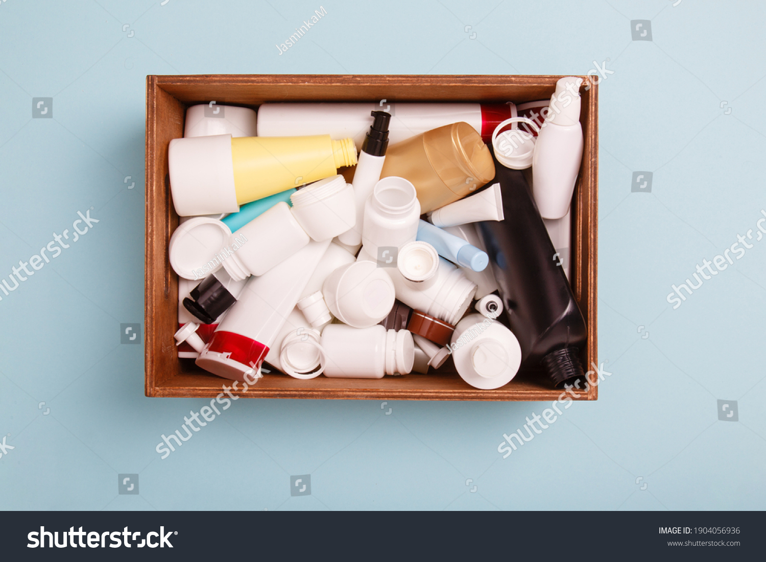 heap of separate collection of HDPE bottles from cosmetics for recycling. High-Density Polyethylene recyclable cosmetics package in a wooden box on blue background. Plastic garbage. Save the planet #1904056936