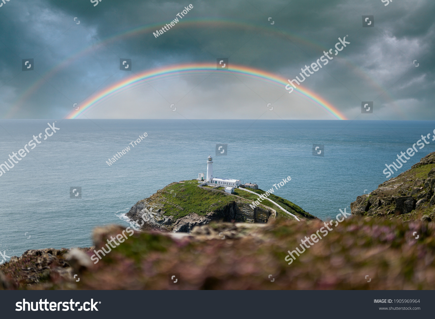 Colourful double rainbows in seascape over the ocean horizon with storm clouds dramatic sky and white lighthouse on top of island peninsular coastline in beautiful calm blue ocean sea south stack #1905969964