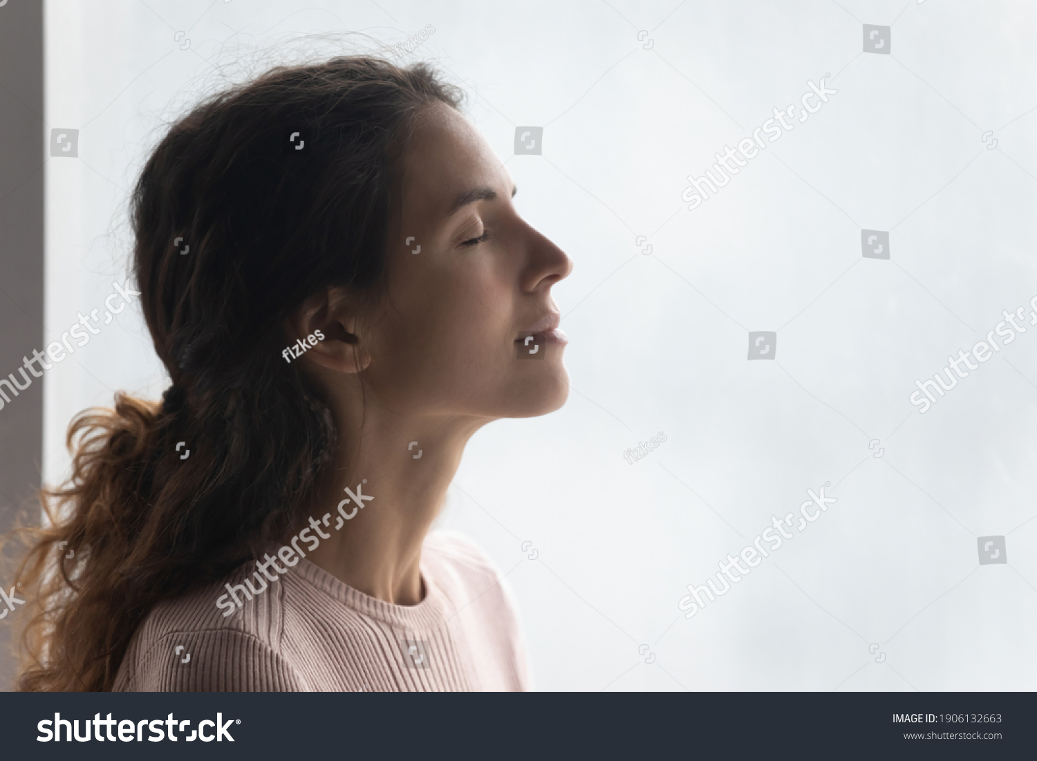 Side head shot view mindful smiling beautiful young woman breathing fresh air, standing near window. Happy millennial caucasian lady enjoying meditation moment, feeling peaceful indoors, copy space. #1906132663