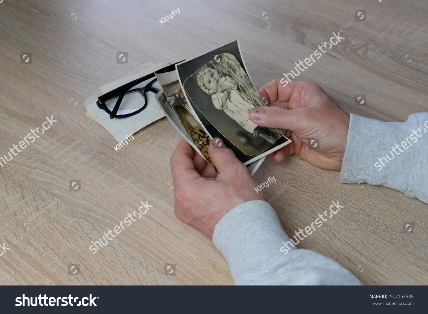 old male hands hold retro family photos over an album with vintage monochrome photographs in sepia color, genealogy concept, ancestral memory, family tree, childhood memories #1907153389