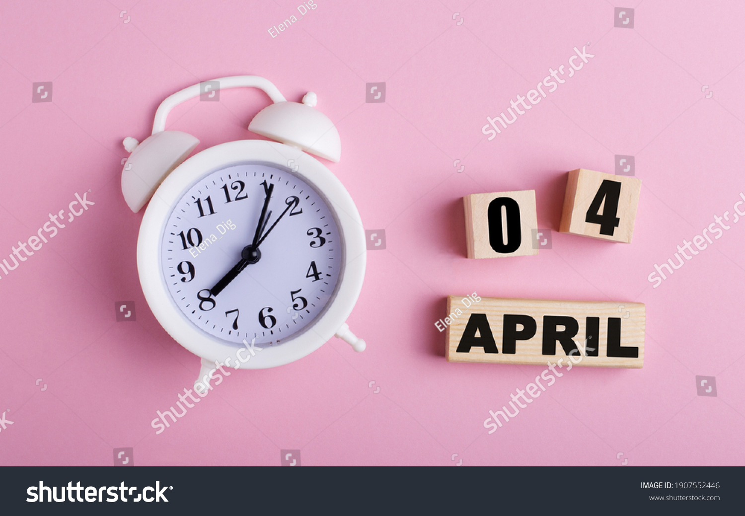 On a pink background, a white alarm clock and wooden cubes with the date of APRIL 04 #1907552446