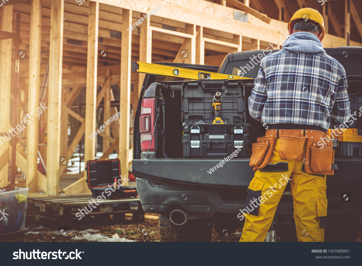 Caucasian Construction Contractor in His 40s and His Modern Black Pickup Truck. Men Preparing His Tools For the Job. Wooden House Skeleton in Background.  #1907689891