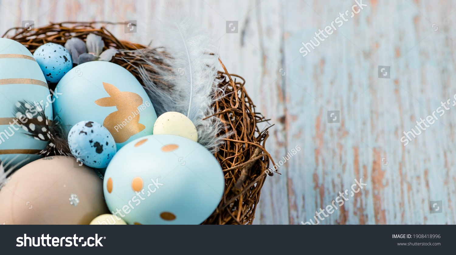 Banner. Easter eggs, feathers in a nest on a blue wooden background. The minimal concept. Top view. Card with a copy of the place for the text. #1908418996
