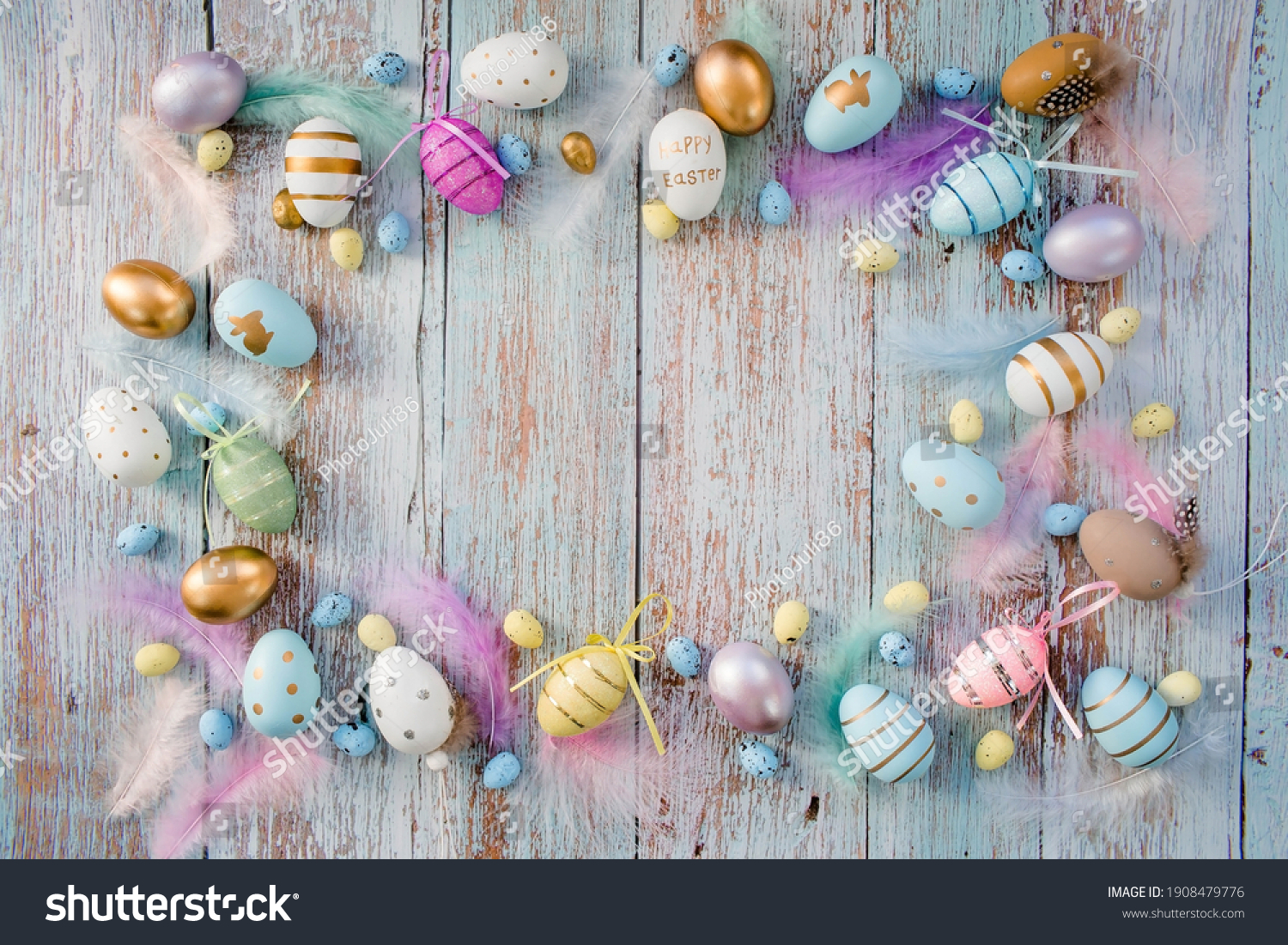 Banner. Easter frame with eggs and feathers on a blue wooden background. The minimal concept. Top view. Card with a copy of the place for the text. #1908479776