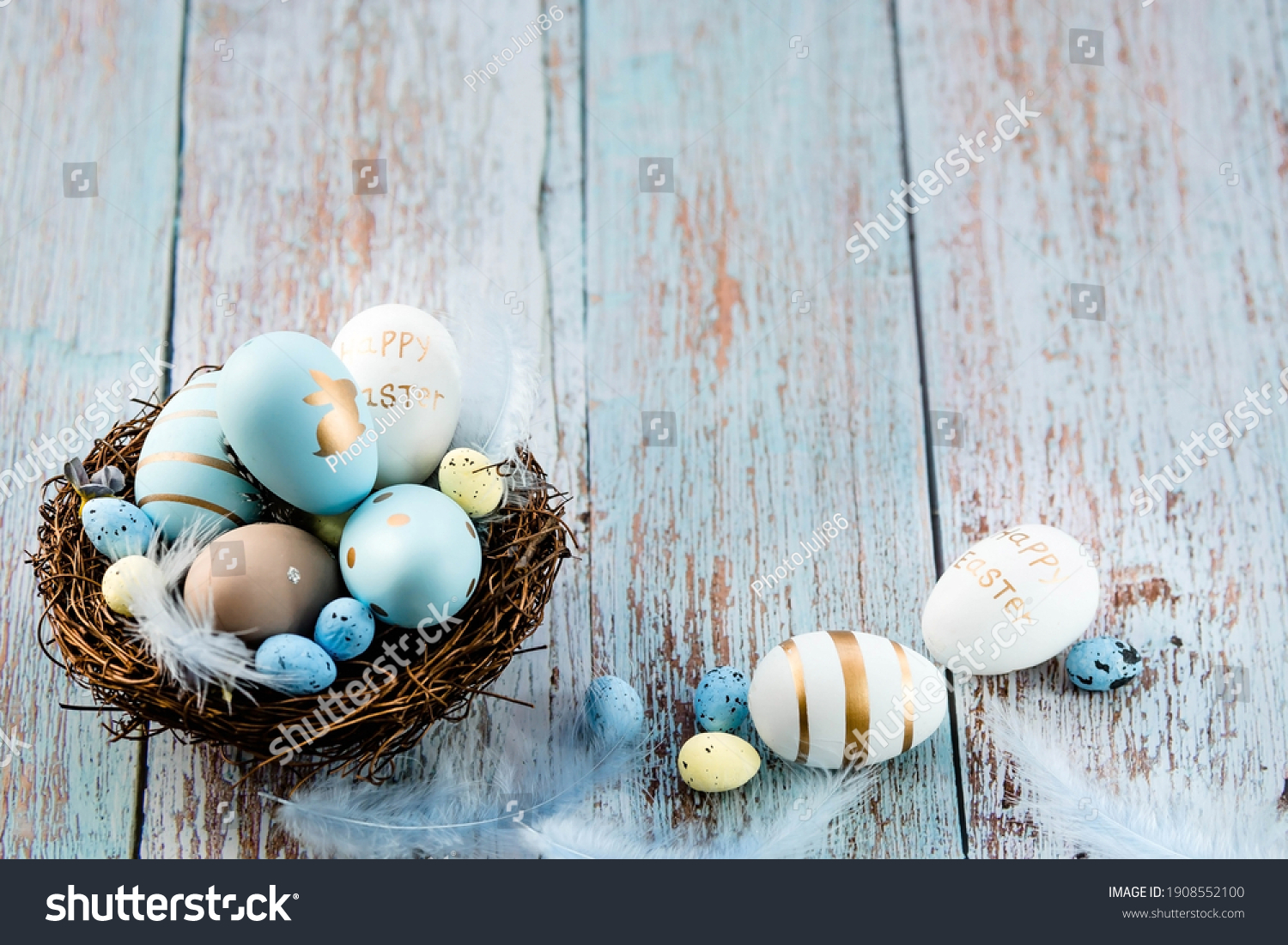 Easter eggs, feathers in a nest on a blue wooden background. The minimal concept. Top view. Card with a copy of the place for the text. #1908552100