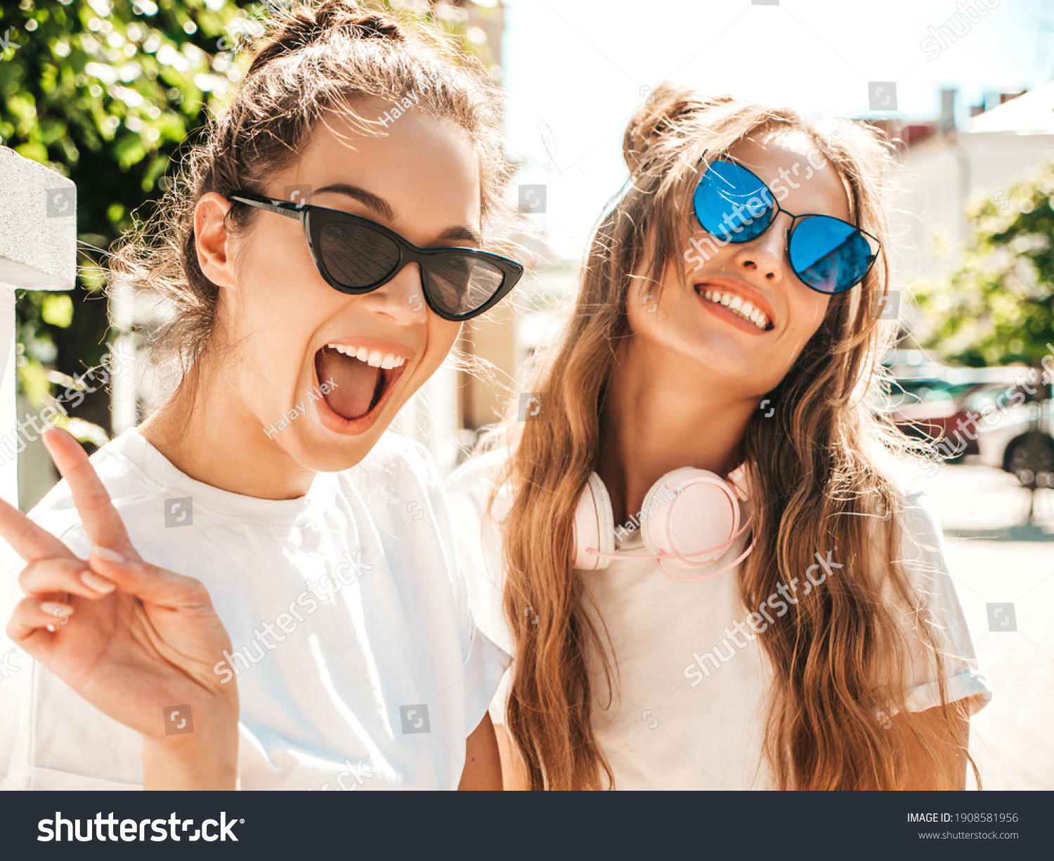 Portrait of two young beautiful smiling hipster female in trendy summer white t-shirt clothes.Sexy carefree women posing on street background. Positive models having fun, hugging and going crazy #1908581956