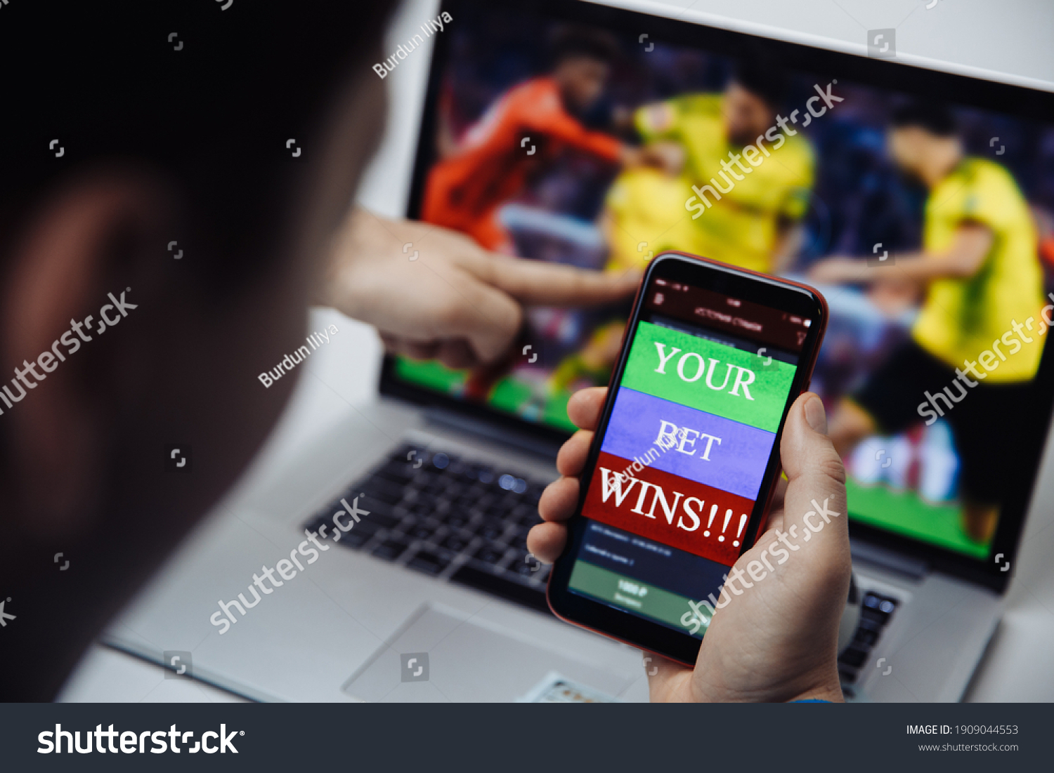 Man watching football online broadcast on his laptop and celebrate victory in betting at bookmaker's website. Betting and gambling concept #1909044553