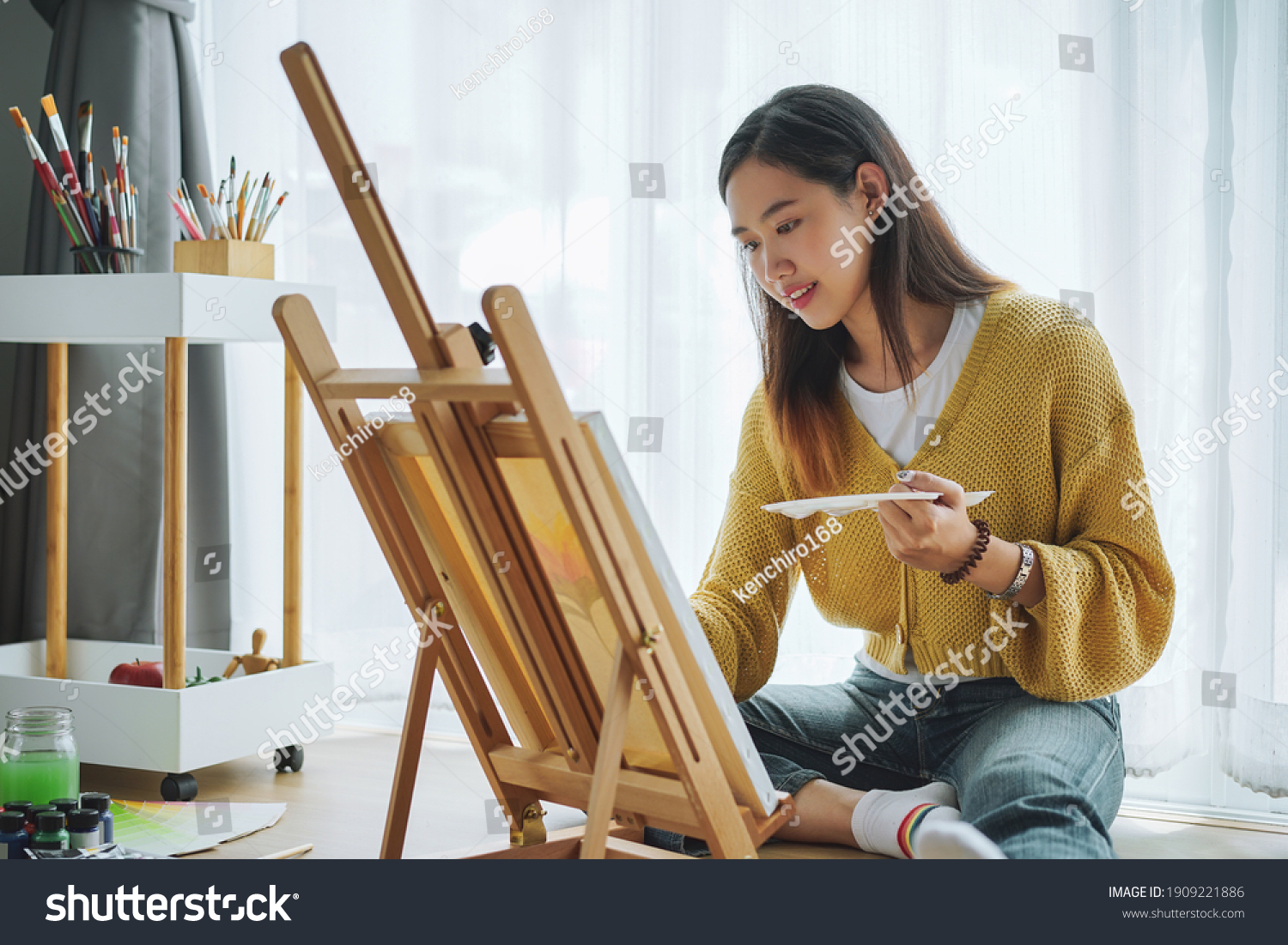 Female artist painting on canvas at home. Hobby and leisure concept. #1909221886