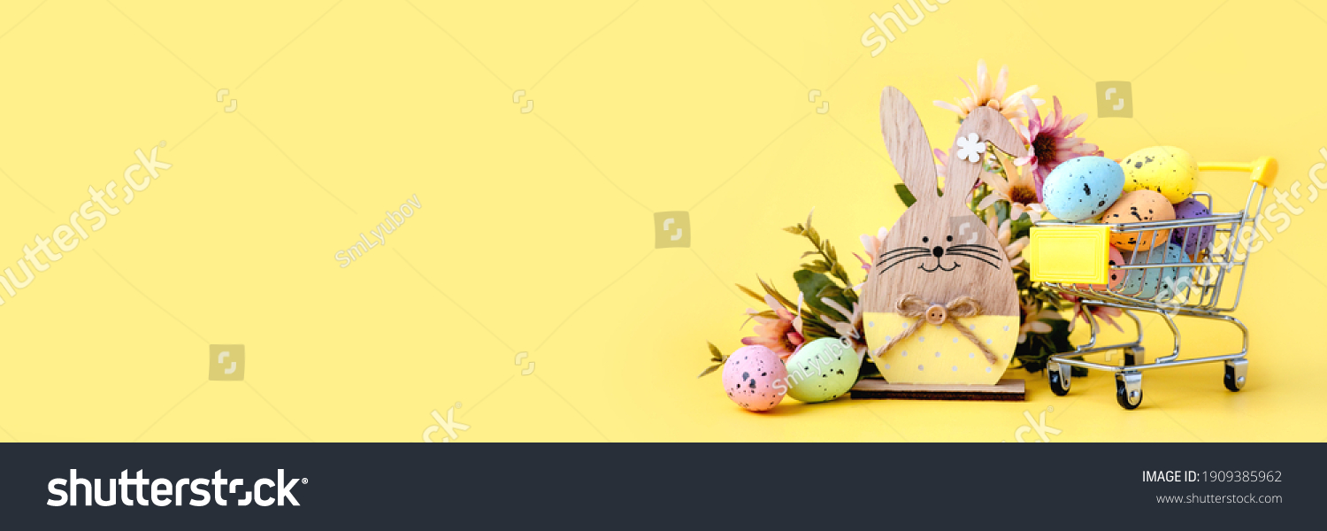 Easter composition with colorful eggs in shopping cart, wooden bunny and spring flowers on yellow background. Banner. Copy space #1909385962