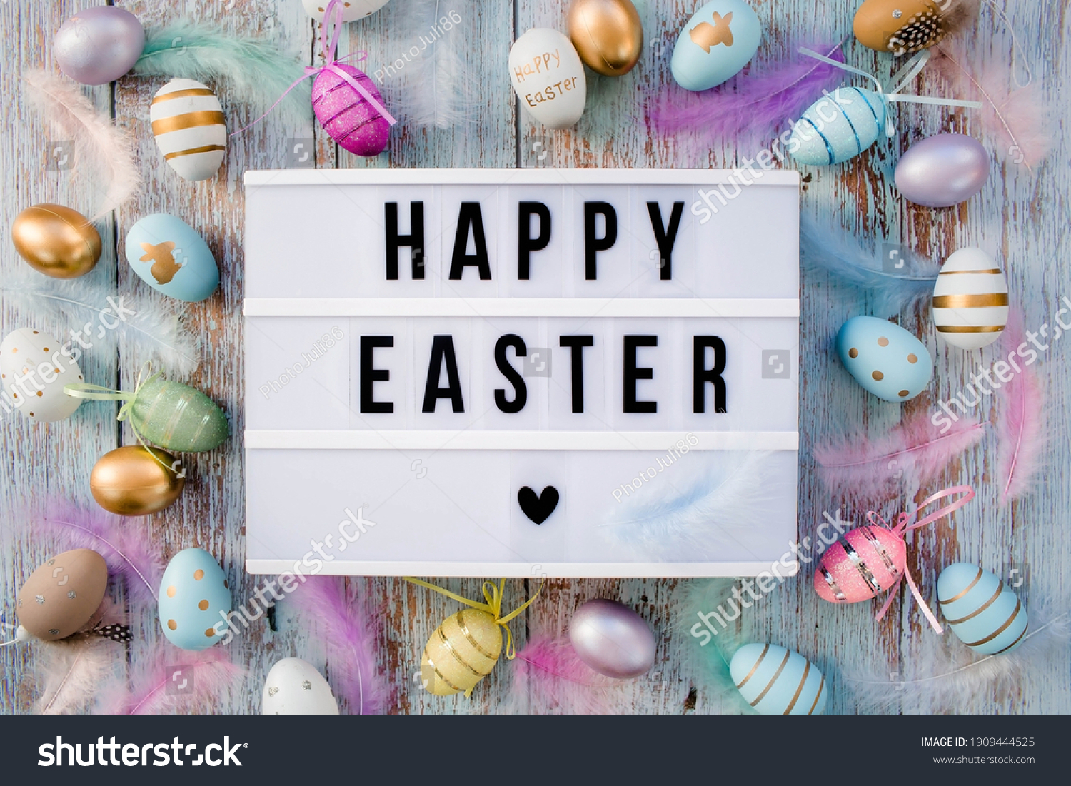Stylish text frame of the lightbox with the inscription happy easter. Pink, blue, white, gold, and yellow eggs are everywhere. Colorful Easter eggs top view. Copyspace. #1909444525