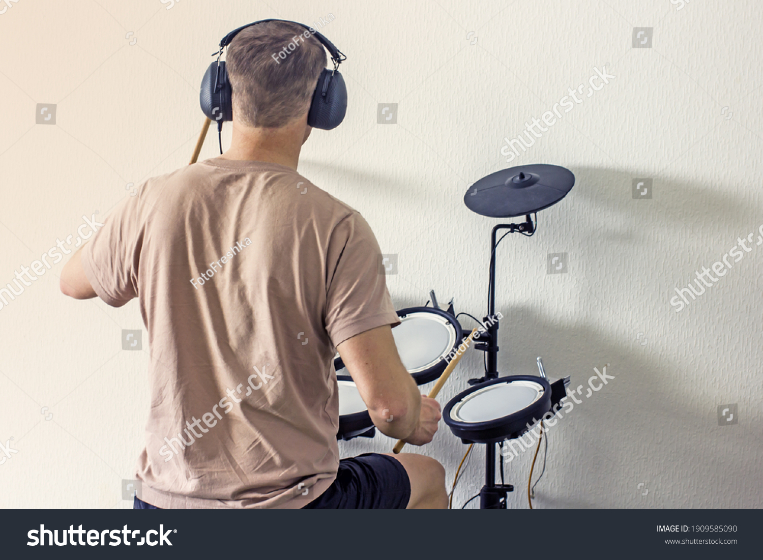 A man without a face in a light T-shirt with headphones and drumsticks playing an electronic drum kit at home, rear view. Home art hobbies authentic concept. Musical hobby drums #1909585090