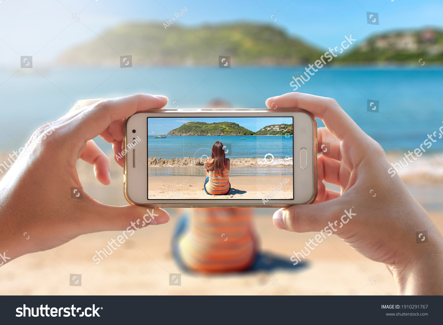 Woman photographing other girl sitting in the beach. She is using to take a photo the camera of a smartphone. A person photographing her friend with a cell phone. #1910291767