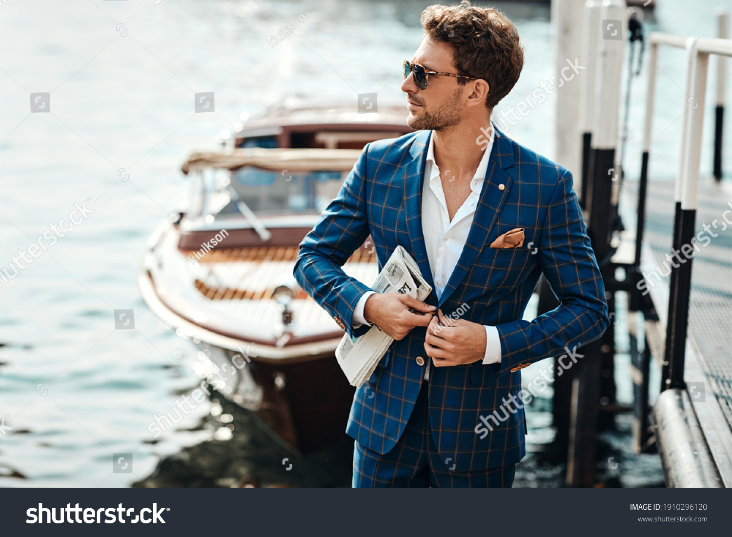 Young handsome man in classic suit over the blurred lake buttoning his jacket #1910296120