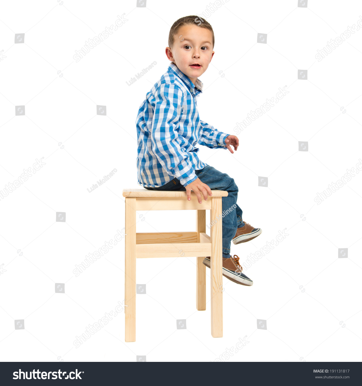 Surprised kid sitting on wooden chair stock photo for Toddler sitting chair
