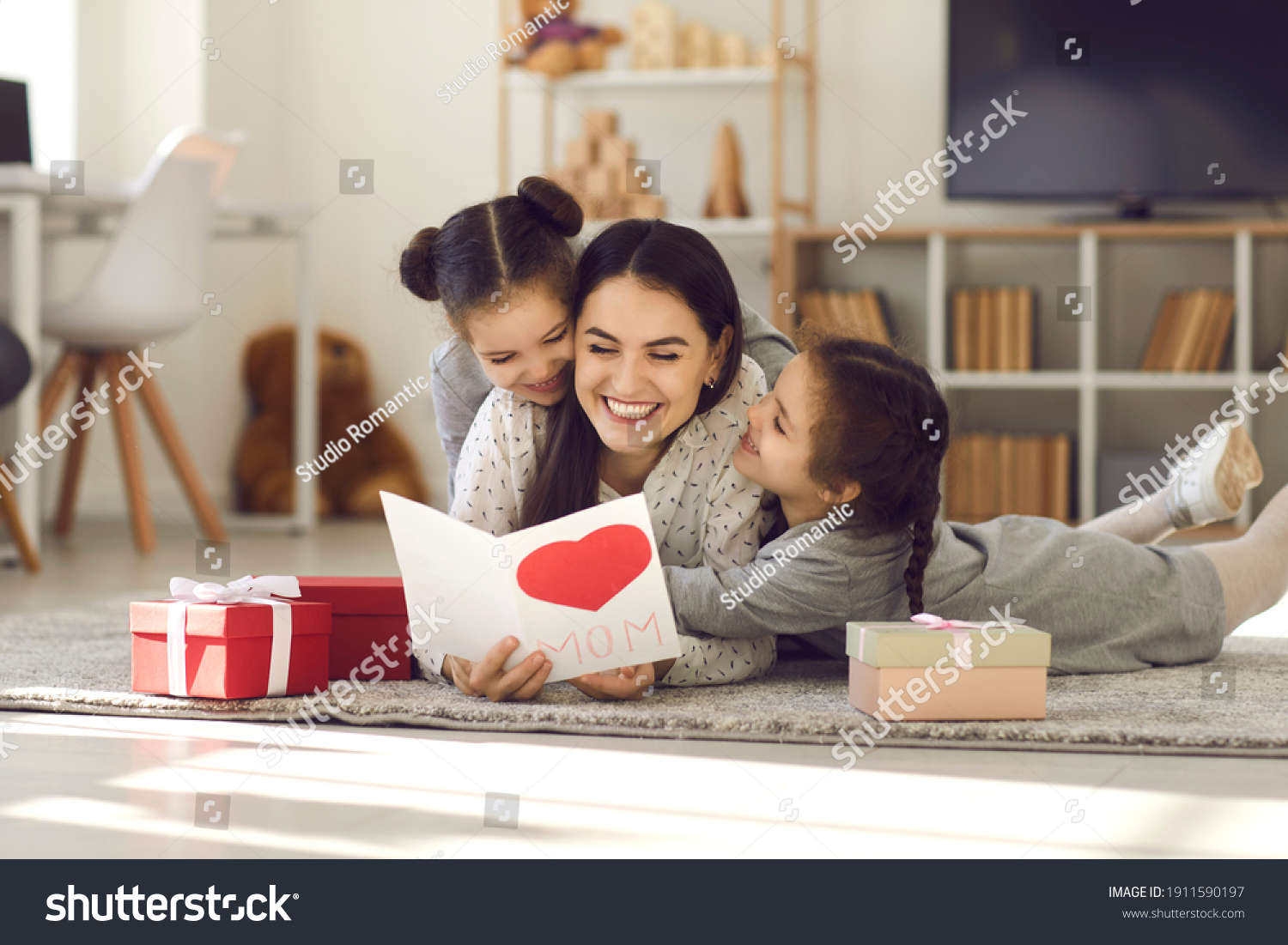 We love you. Smiling young woman getting presents from kids. Two cute twin daughters giving mom handmade greeting card. Little children lying on floor, hugging mommy and wishing her Happy Mother's Day #1911590197