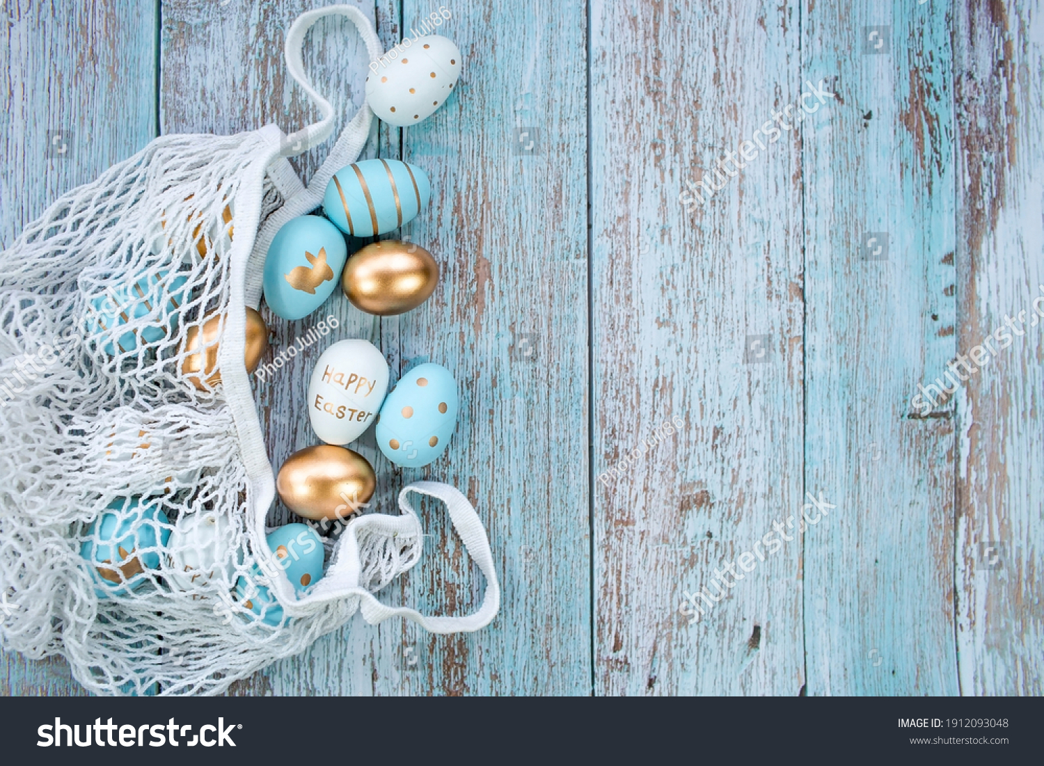 Gold, black, white, blue  eggs in a string bag on a blue wooden background. Geometry. The minimal concept. Top view. An Easter card with a copy of the place for the text. #1912093048