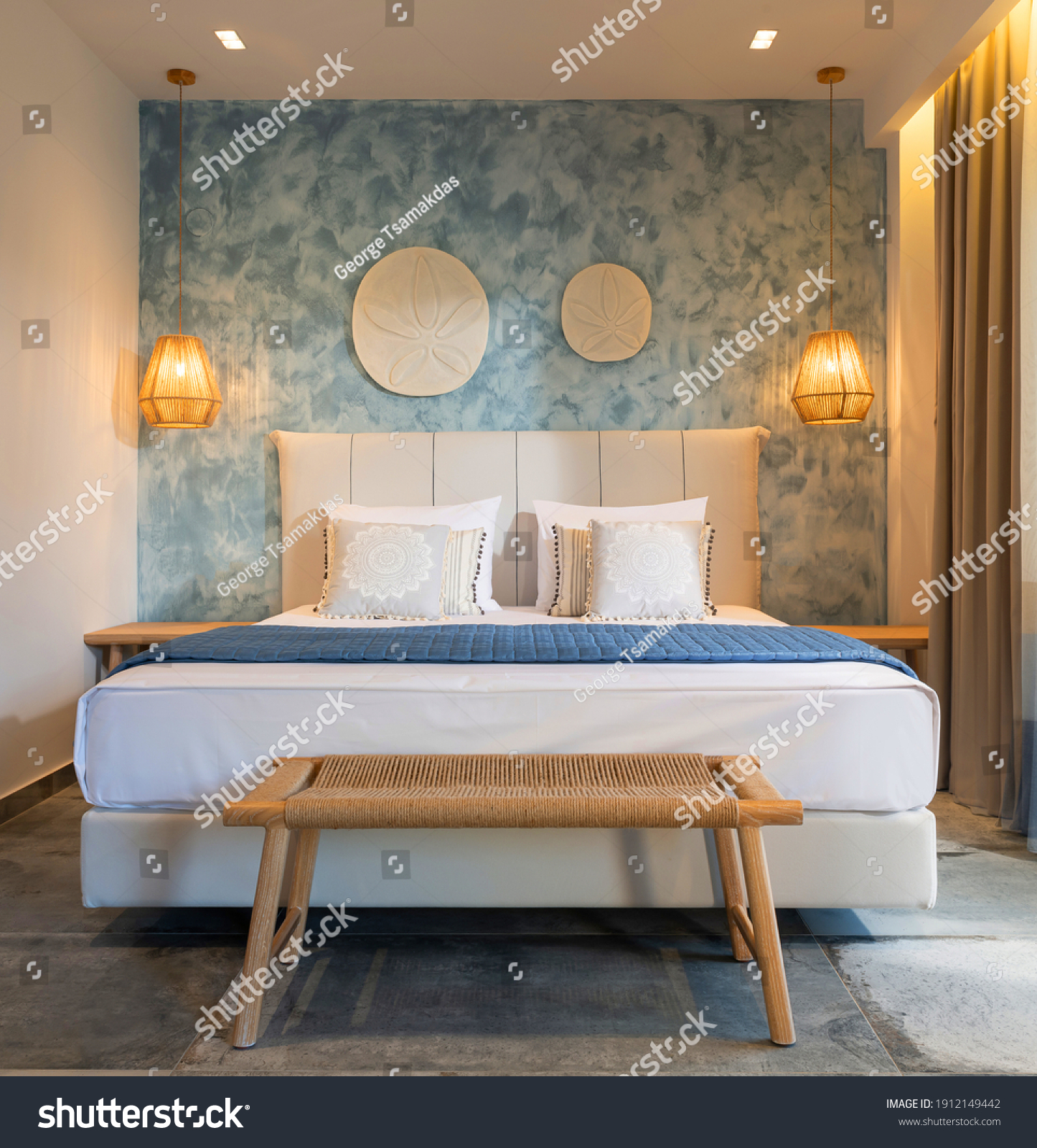 Front view of modern bedroom interior in nautical marine style with blue decorative stucco wall, wicker furniture, ceiling wooden lamps, white soft bed #1912149442