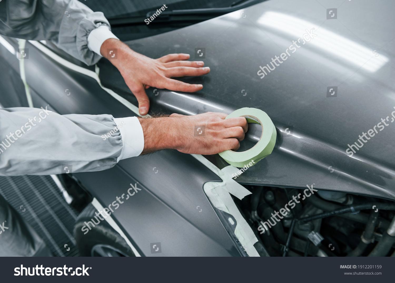 Detailed work. Caucasian automobile repairman in uniform have job in garage. #1912201159