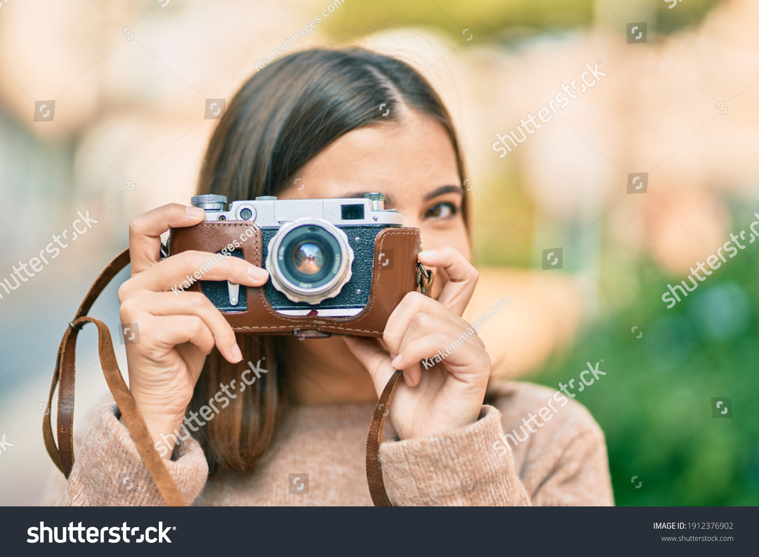 Young hispanic tourist woman smiling happy using vintage camera at the city. #1912376902