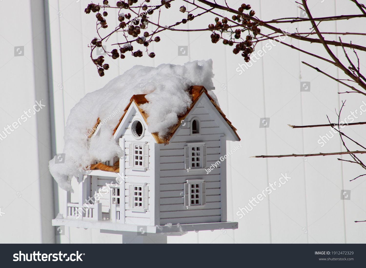 A detailed, white colonial birdhouse with a cedar shingle roof covered in snow and hiding under a bush filled with berries for cover.  The entrance hole just above the detailed porch is for songbirds.