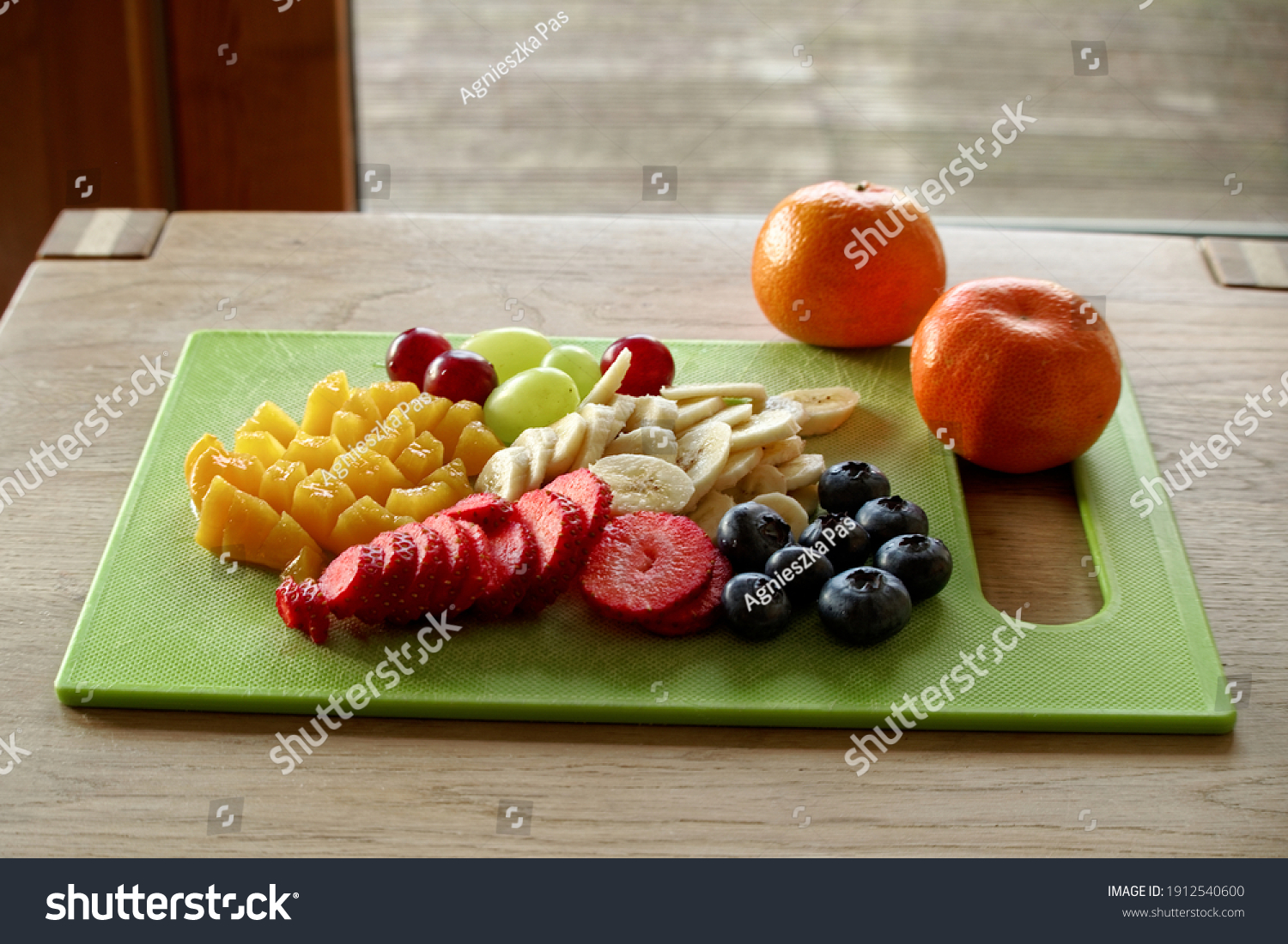Sliced fruits on cutting board on a wooden table. Healthy, fresh and colorful ingredients for fruit salad or breakfast. Bright colors. View from above. Selective focus.