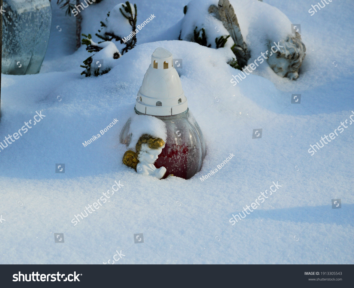 stock-photo-a-candle-and-angel-snow-cove