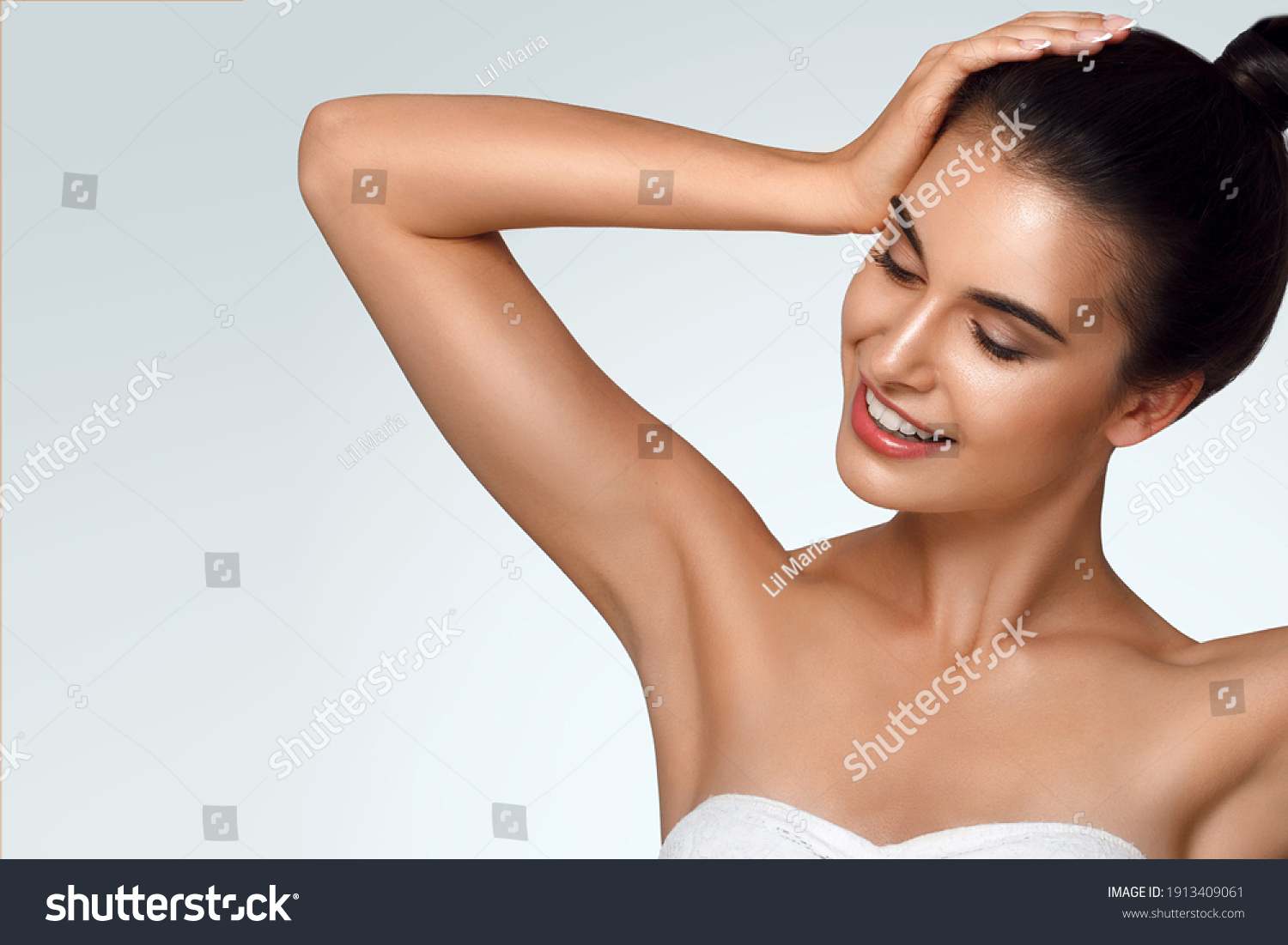 Caucasian beautiful girl holds hair in hand, raise up hands. Beauty young woman, salon body and armpit skin care, smooth armpit skin, hair removal and sugaring. Happy girl with closed eyes #1913409061