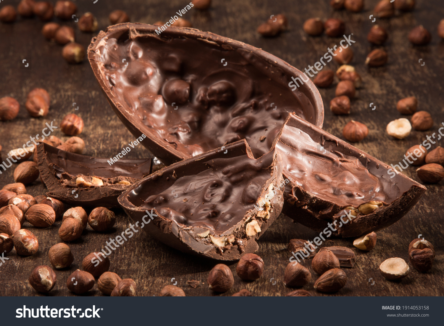 Stuffed chocolate easter egg on a wood table with hazelnuts. #1914053158