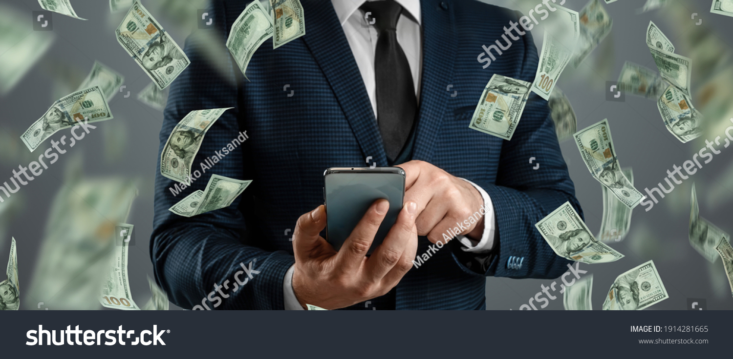 Online sports betting. A man in a suit is holding a smartphone and dollars are falling from the sky. Creative background, gambling #1914281665