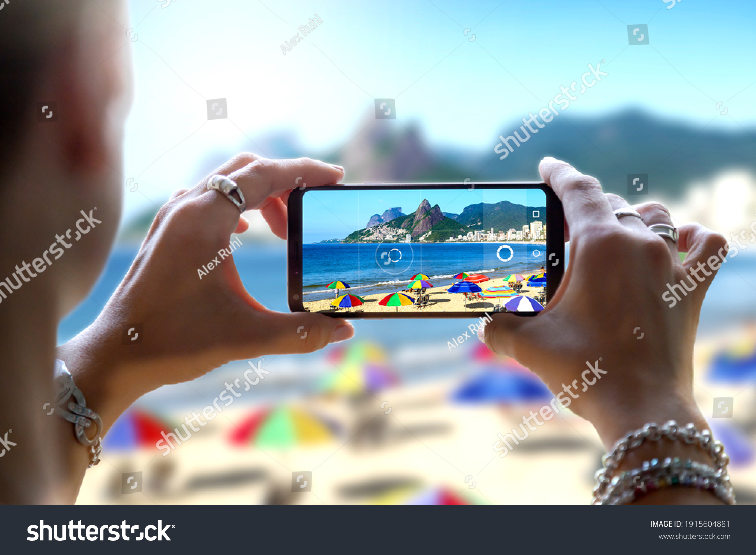 Woman in Ipanema Beach taking a photo with her mobile phone. Photographing with a camera of a smartphone in Rio de Janeiro, Brazil. #1915604881
