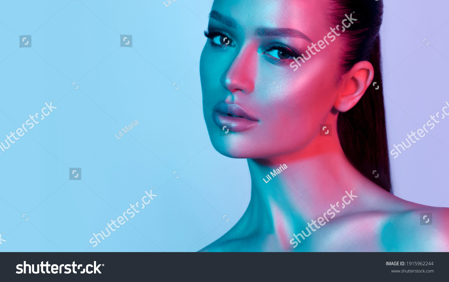 High fashion model metal silver lips and face woman in colorful bright neon UV blue and purple lights, posing in studio, beautiful girl, glowing makeup, colorful makeup. Glitter Bright Neon Makeup #1915962244