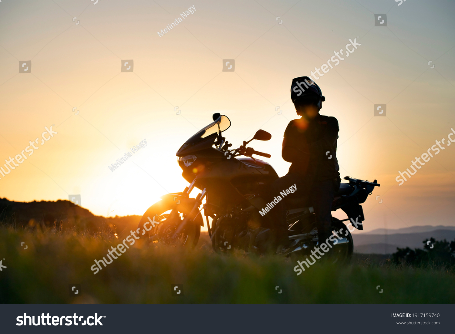Young motorcycle rider on the road with sunset light background. #1917159740