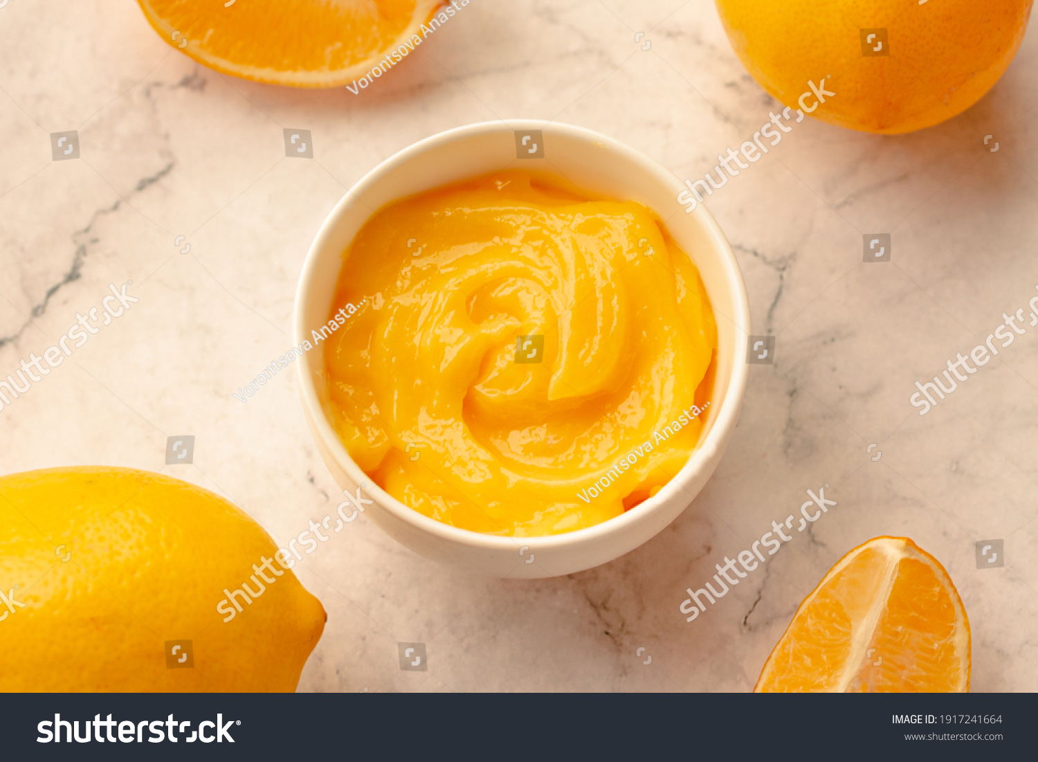 Delicious homemade tangy lemon curd decorated with fresh fruit on marble background.Top view. #1917241664