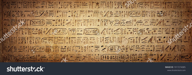 Old Egyptian hieroglyphs on an ancient background. Wide historical background. Ancient Egyptian hieroglyphs as a symbol of the history of the Earth.  #1917274085
